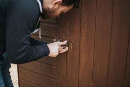 man in black pullover jacket picking lock